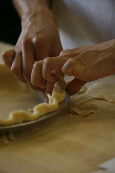 Staff writer Janny Hu crimps the dough for a Best Way Piecrust in the Chronicle test kitchen.