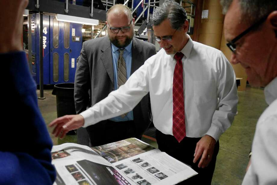 Dave King, left, editor/associate publisher of The Alt, a new alternative weekly, and John DeAugustine, president and publisher of the Schenectady Gazette, look over early copies of the publication inside the press room at the Schenectady Gazette on Monday, Nov. 14, 2016, in Schenectady, N.Y.    (Paul Buckowski / Times Union) Photo: PAUL BUCKOWSKI / 20038794A