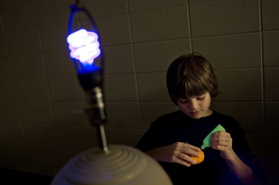 While sitting next to a black light, Midlander Gavin Fields, 10, decorates a small pumpkin during with glow paint during Science CafŽ: Glow Night on Monday at the Midland Center for the Arts. Participants got to decorate a pumpkin or an ornament with materials that glow under black lights. Dr. Greg Colores, associate professor of biology at Central Michigan University and biochemist Dr. Gina Malczewski gave presentations about fluorescence, phosphorescence, and chemi- and bio-luminescence of living things. After the presentations guests broke into groups and participated in glow-in-the-dark activities. Photo: NICK KING ,  Nking@mdn.net