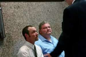 Coty Bob McDonnell, in white shirt, listens to his lawyer, Daniel De La Garza, after a court hearing in McDonnell's case last November. McDonnell was charged with deadly conduct after detaining four men with an AR-15 because he believed they were going to break into the home of his neighbor, Doug Stearns, who is seated next to McDonnell.