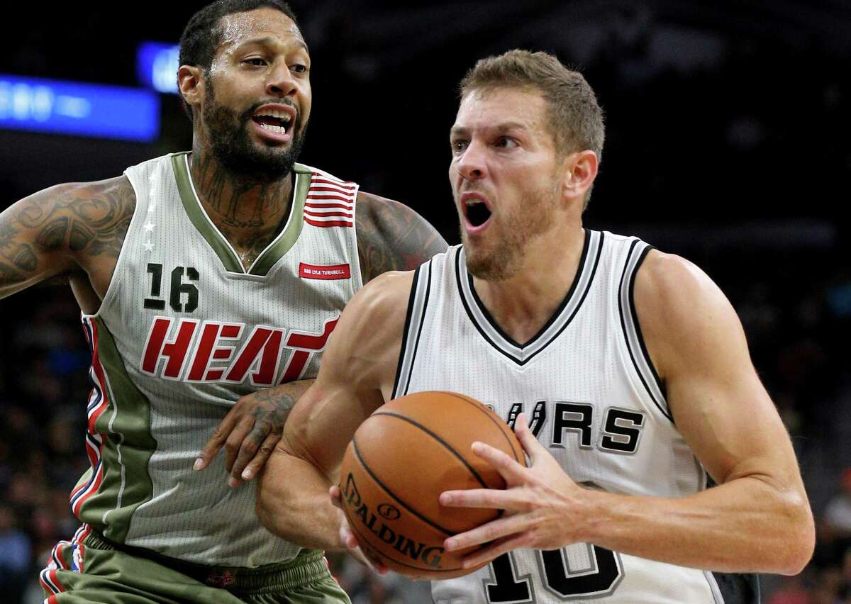 David Lee looks for room inside around Miami's James Johnson during a victory on Nov. 14 at the AT&T Center.