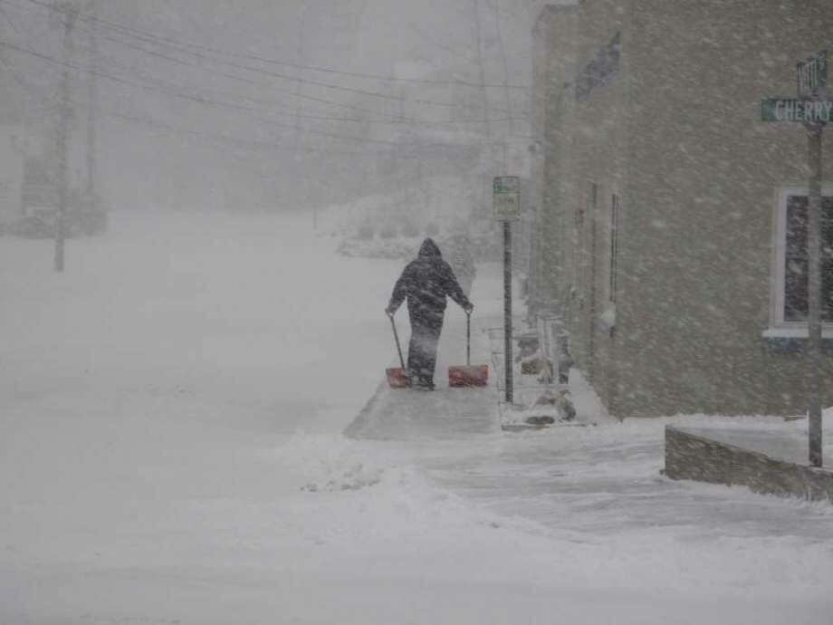 A man pushes two shovels outside New Canaan Veterinary Hospital as wind and snow whip at him during the blizzard on Dec. 26, 2010. Photo: /