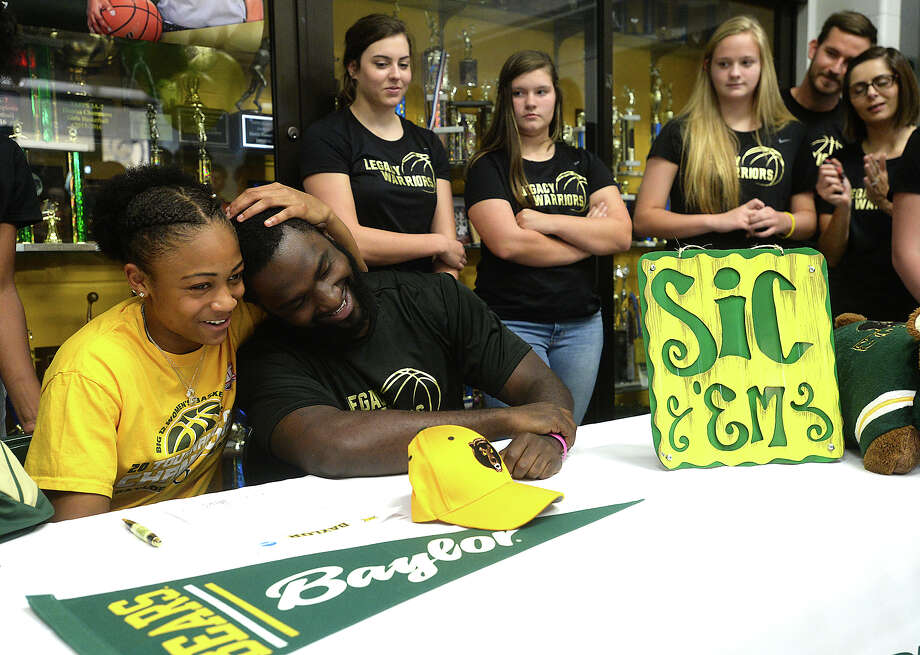 Legacy Christian Academy's Alexis Morris signs her commitment letter to Baylor University Monday as teammates, family, coaches, and classmates fill the lobby of the gymnasium to watch and congratulate her. Morris was joined at the signing table by her sisters Ashari Morris (left) and Aerius Morris, and by (from left) her godfather Albert Dill, on behalf of her father Raymond Morris, mother Sharonne Morris, and stepfather Markus Robinson. Refreshments were served following the signing and photos. Photo taken Monday, November 14, 2016 Kim Brent/The Enterprise Photo: Kim Brent / Beaumont Enterprise