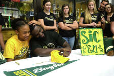 Legacy Christian Academy's Alexis Morris signs her commitment letter to Baylor University Monday as teammates, family, coaches, and classmates fill the lobby of the gymnasium to watch and congratulate her. Morris was joined at the signing table by her sisters Ashari Morris (left) and Aerius Morris, and by (from left) her godfather Albert Dill, on behalf of her father Raymond Morris, mother Sharonne Morris, and stepfather Markus Robinson. Refreshments were served following the signing and photos. Photo taken Monday, November 14, 2016 Kim Brent/The Enterprise