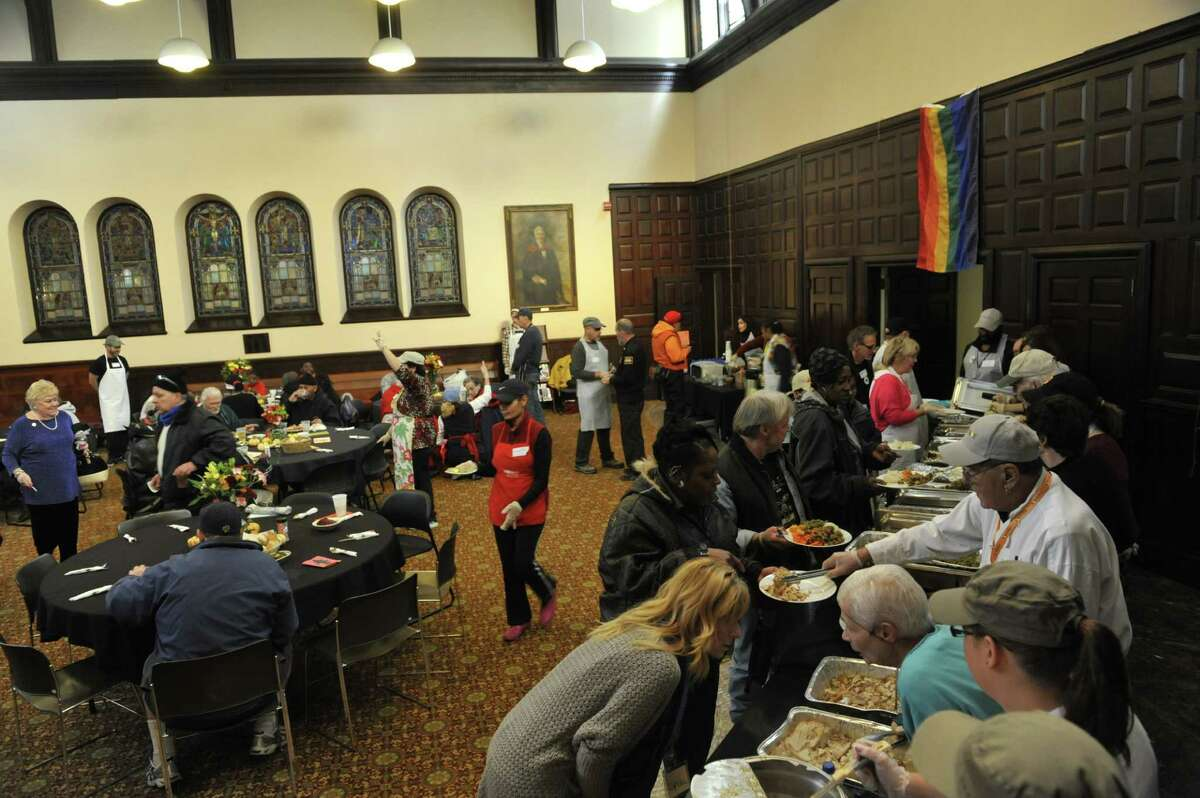 Volunteers help serve as guests enjoy a meal at the annual Equinox Thanksgiving Day Community Dinner at First Presbyterian Church on Thursday, Nov. 26, 2015, in Albany, N.Y. (Paul Buckowski / Times Union)