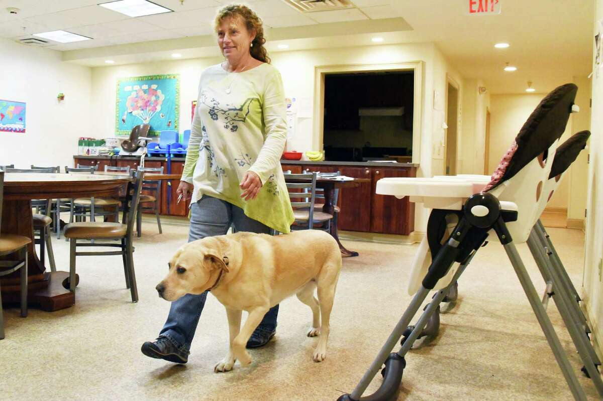 St. Paul's Center executive director Tracy Pitcher and therapy dog Samantha in the center's dining room Wednesday Oct. 19, 2016 in Rensselaer, NY. (John Carl D'Annibale / Times Union)