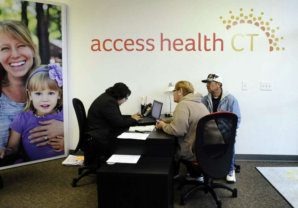 Gildred Ortiz, center and Julio Colon, right, receive help from outreach worker for Access Health CT, Cristela Solorio Ruiz during a grand opening for Connecticut's health insurance exchange's first insurance store, Thursday, Nov. 7, 2013, in New Britain, Conn. Existing Access Health CT customers can still shop and renew their healthcare coverage during open enrollment which began Nov. 1 and ends Jan. 31, 2017. (AP Photo/Jessica Hill)