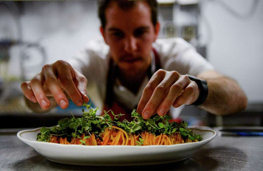 William Wright dresses a dish during at Arthur Ave Photo: Erin Hull / Erin Hull