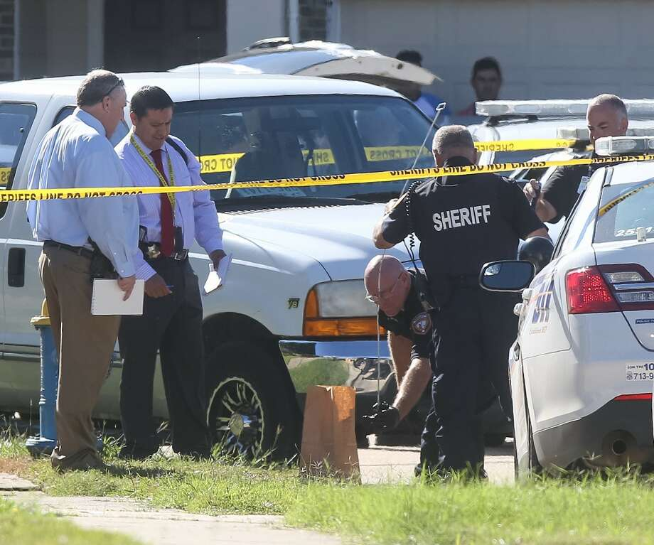 Investigators retrieve a firearm from a drain at the scene of a homicide that occurred on Blossombury Court, Tuesday, Nov. 15, 2016, in Katy. Photo: Jon Shapley | Houston Chronicle