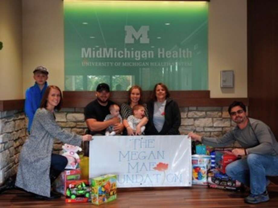 Three-year-old Jase Groulx, (center of photo held by mom, Sam) and other members of his family recently stopped by MidMichigan Medical Center - Midland to donate his birthday gifts to children seeking cancer treatment.