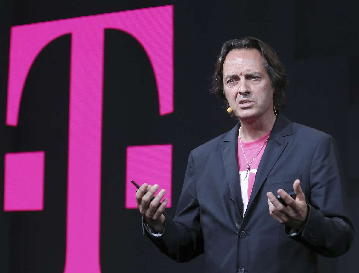 """In this Wednesday, July 10, 2013, file photo, T-Mobile CEO John Legere speaks during a news conference, in New York. CEOs of major companies are taking stands about the results of the November 2016 U.S. election, a departure from the traditional model of not mixing politics with business that the major brands have long espoused. Legere tweeted """"let's see what an out of the box, non-typical, non-politician can do for America!"""" (AP Photo/Mary Altaffer, File)"""