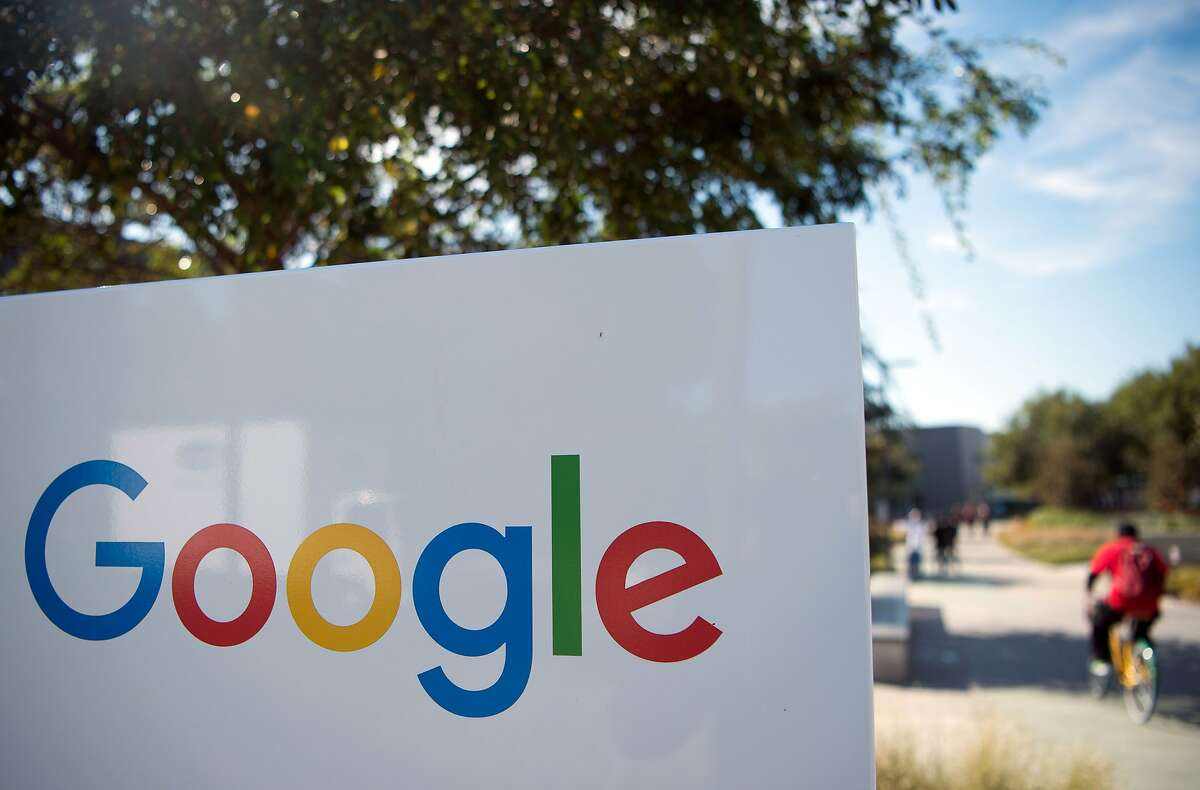 (FILES) This file photo taken on Nov. 4, 2016 shows a man riding a bike past a Google sign at the Googleplex in Menlo Park. Google and Facebook moved November 15, 2016 to cut off advertising revenue to bogus news sites, acting after criticism of the role fake news played in the US presidential election.