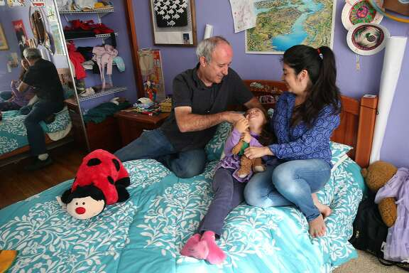 Dale Duncan and his wife Marta Munoz play with their 6-year-old daughter Emilia at their Mission District apartment in San Francisco, Calif. on Wednesday, June 3, 2015. Duncan, who's lived in the same unit for 21 years, is battling eviction by a controversial landlord that purchased the building last year.