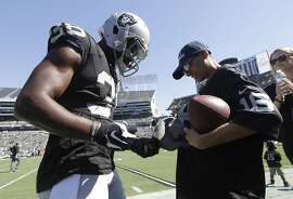Oakland Raiders cornerback T.J. Carrie (38) signs autographs before an NFL football game against the San Diego Chargers in Oakland, Calif., Sunday, Oct. 9, 2016. (AP Photo/Marcio Jose Sanchez)