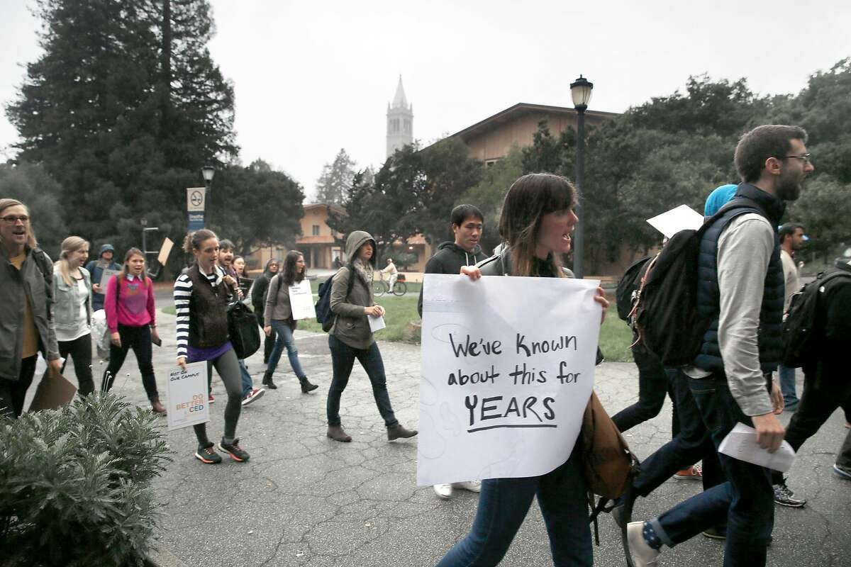 UC Berkeley graduate student in public health and city planning Sarah Skenazy (with large white sign) protests university rules surrounding sexual harassment investigations outside of Wurster Hall at UC Berkeley on Tuesday, November 15, 2016, in Berkeley, Calif.