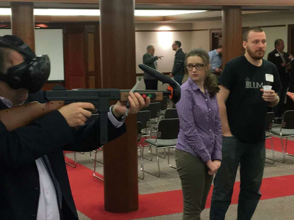 Michael Lobsinger, left, of the Center for Economic Growth tests out a virtual reality video game gun controller designed by Illium VR of Troy at the VentureB event at Rensselaer Polytechnic Institute. At right is Jazmine Olinger and Sebastian Sarbora, both of Ilium VR. Source: Larry Rulison