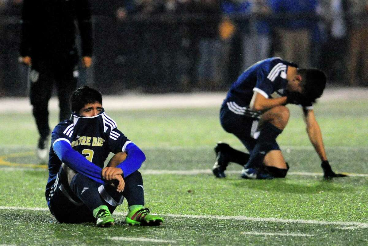 Notre Dame of Fairfield's Kevin Morataya sits on the field dejected with another temmate after the team was defeated by Old Saybrook 3-2 after Class S boys soccer semi-final action in West Haven, Conn. on Tuesday Nov. 15, 2016.