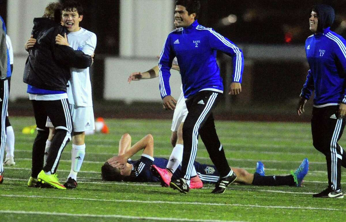 Notre Dame of Fairfield's Colin Burke lays on the field dejected as Old Saybrook celebrates its win after Class S boys soccer semi-final action in West Haven, Conn. on Tuesday Nov. 15, 2016. Final score was 3-2.