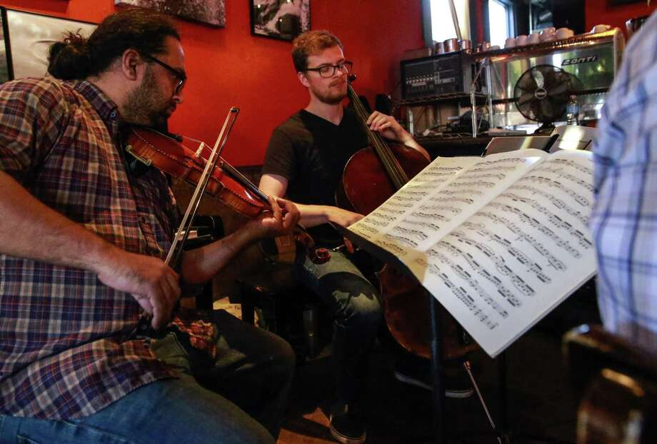 Classical Revolution founder Charith Premawardhana plays violin alongside cellist James Jaffe at the Revolution Cafe. / ONLINE_YES