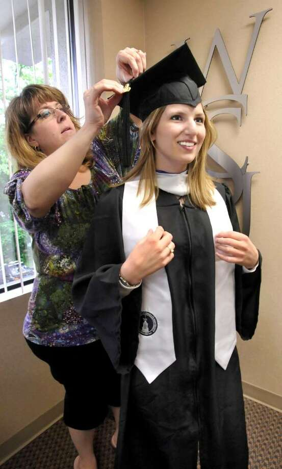 Tammy Haqmmershoy, director of alumni relations at WESTCONN, helps Lisa Mancini, 22, try on one of the first ever recycled graduation gowns on Wednesday, May 19, 2010. The recycled gowns are offered to graduate students who will receive diplomas on Friday and ungergraduates who will receive theirs on Sunday. Photo: Michael Duffy / The News-Times