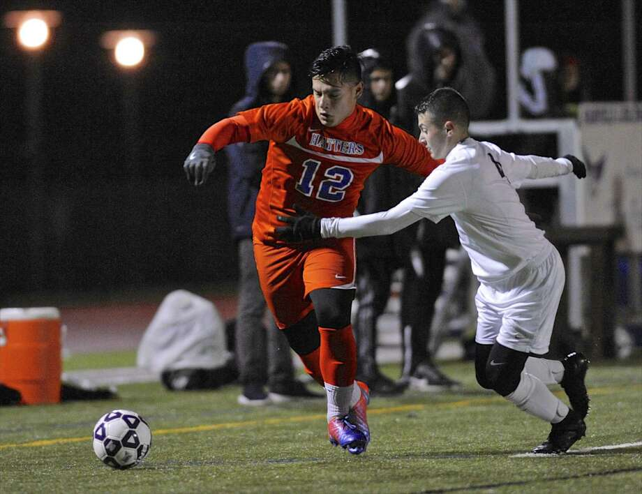 Danbury's Arnold Gallcia (12) and Shelton's Anthony Russo (4) battle for the ball in the Class LL boys soccer state semifinal game between Shelton and Danbury high schools Tuesday night at Fairfield-Ludlow High School, Fairfield, Conn. Photo: H John Voorhees III / Hearst Connecticut Media / The News-Times