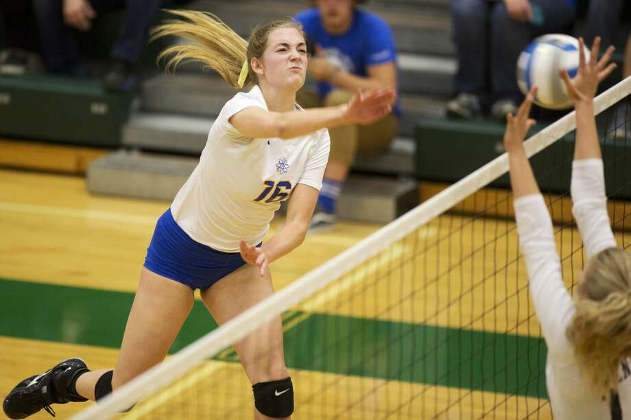 Midland High School senior Ellie Jensen spikes the ball toward Fenton High School defenders in the Class A volleyball quarterfinals at Dow High School on Tuesday. Photo: Theophil Syslo
