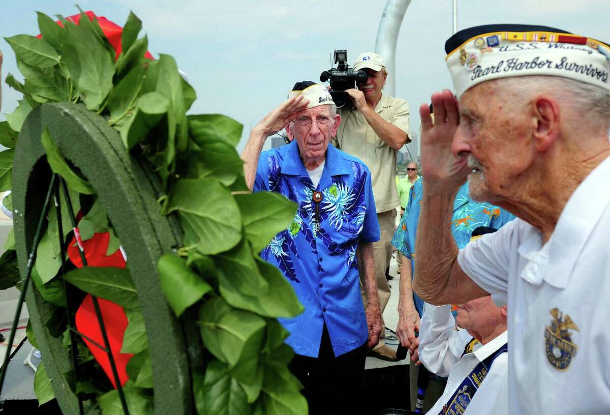 Navy veterans Floyd Welch, 91, of East Lyme, left, and Jack Stoeber, 96, of Milford, salute the wreath during a dedication at the new Pearl Harbor Memorial Bridge Friday, June 22, 2012 in New Haven, Conn.