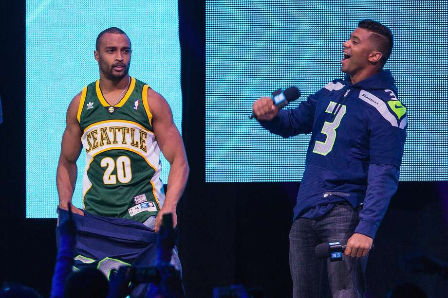 Seattle Seahawks player Doug Baldwin reveals his Seattle Supersonics jersey with quarterback Russell Wilson during We Day at KeyArena on April 23, 2015 in Seattle, Washington. Photo: Mat Hayward/Getty Images