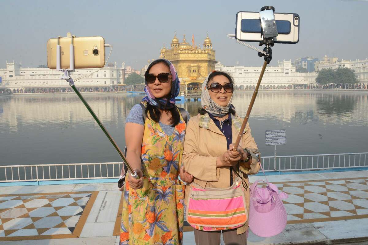 Chinese tourists take a 'selfie' at the Golden Temple in Amritsar on November 14, 2016, as Sikh devotees mark the 547th birth anniversary of Sri Guru Nanak Dev.