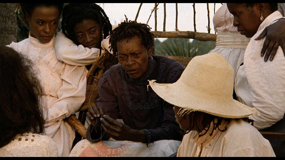 """Above: Cora Lee Day, center, plays a matriarch whose family is preparing to join the Great Migration north in """"Daughters of the Dust."""" At right: Julie Dash, the film's director. Photo: Cohen Film Collection"""