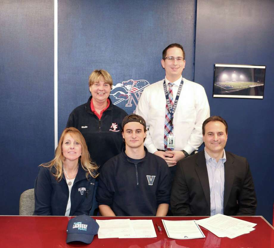 New Fairfield High School lacrosse star Michael Clark, front center, signed a National Letter of Intent to play lacrosse at Villanova University at a ceremony at the high school on Nov. 9. Clark is flanked by his mother Peg, left, and his father Ken, right. Behind them are New Fairfield High Athletic Director Mary Stolle, back left, and New Fairfield High Principal Dr. Richard Sanzo, back right. Photo: Contributed Photo / Contributed Photo