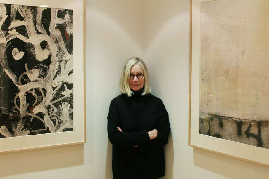 """Joyce Seymore standing between two photos of her recent collection, """"From the Walls of Rome"""" — which will appear in Wilton Library's upcoming art exhibit, """"The Message is in the Medium."""" Photo: Stephanie Kim / Hearst Connecticut Media"""
