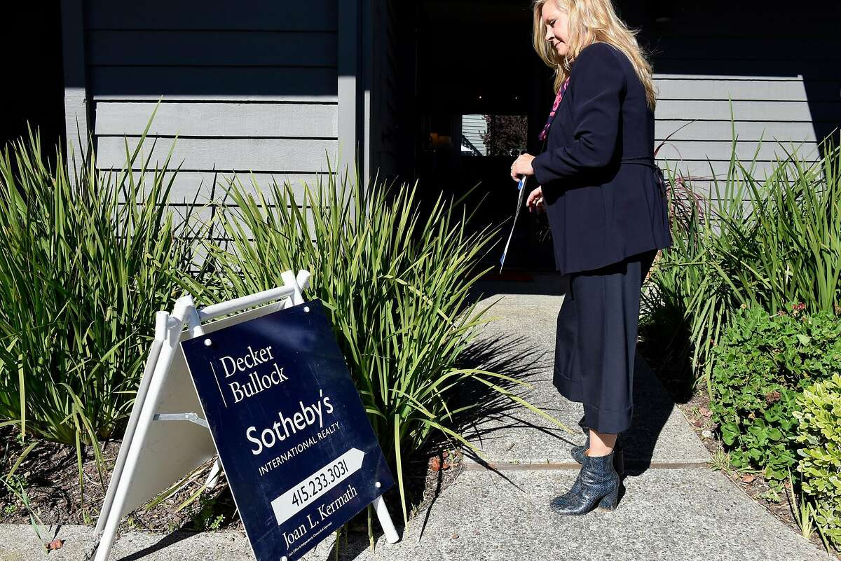 Realtor Joan Kermath of Sotheby's International Reality adjusts a sign while hosting a broker's open house for a condo in Sausalito, CA Wednesday, November 16, 2016.