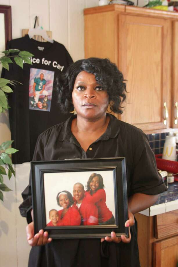 Rhonda Wills holds up a photo of her family from happier times. Five years ago, her son Carl, 22, was murdered and his body was dumped on a rural road in Liberty County. The murder remains unsolved. Photo: Vanesa Brashier