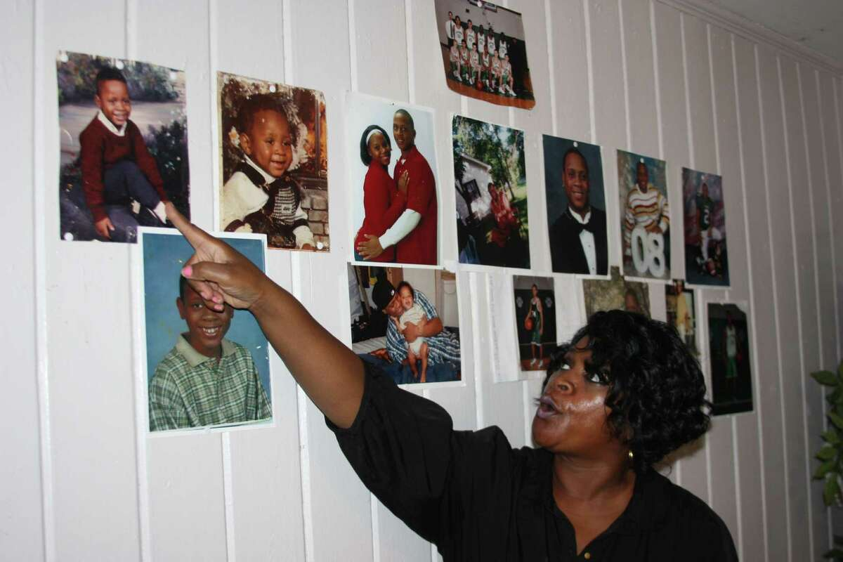 Rhonda Wills points to the photos of her son, Carl, on the living room wall of her Livingston home. Carl was murdered in late summer of 2011. His body was found in a ditch alongCR 2132, which is also known as Plantation Road, in north Liberty County.