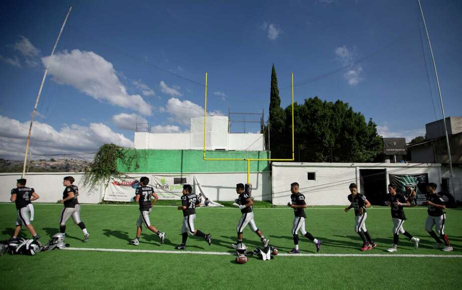 In this Nov. 5, 2016 photo, football players from the Raiders youth squad warm up before a game against the Buhos on the outskirts of Mexico City. They are one of dozens of teams that every Saturday go out and plays football instead of soccer in a country that, according to the NFL, has around 25 million fans. (AP Photo/Eduardo Verdugo) Photo: Eduardo Verdugo, STF / Copyright 2016 The Associated Press. All rights reserved.