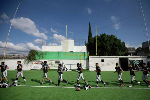 In this Nov. 5, 2016 photo, football players from the Raiders youth squad warm up before a game against the Buhos on the outskirts of Mexico City. They are one of dozens of teams that every Saturday go out and plays football instead of soccer in a country that, according to the NFL, has around 25 million fans. (AP Photo/Eduardo Verdugo)