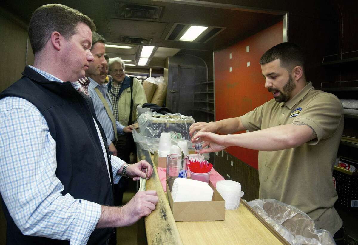 A bartender pour drinks for commuters on a Metro-North bar car on the last night of the