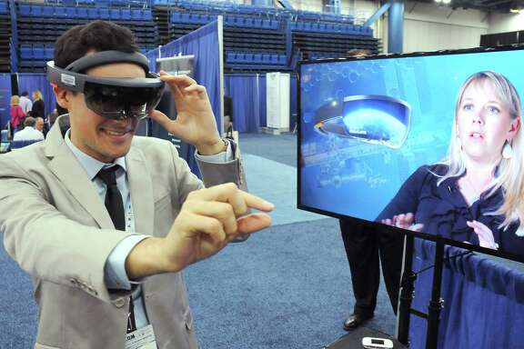 Robin Faideau from the French Office for Science and Technology tries out virtual reality goggles from Aexa at SpaceCom at the George R. Brown Convention Center Wednesday  Nov. 16, 2016.(Dave Rossman photo)