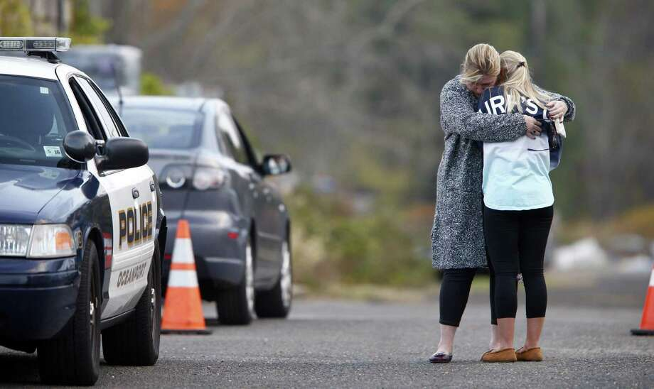 A woman, who police identified as a friend of the victim, is consoled by another woman on the long driveway that leads to the rear of the Froggia Florist and Greenhouses in Oceanport, N.J, where the body of Joseph Comunale, a missing Hofstra University graduate originally from Connecticut, was reportedly found Wednesday, Nov. 16, 2016. Photo: Thomas P. Costello / The Asbury Park Press Via AP / Gannett NJ / USA Today Network