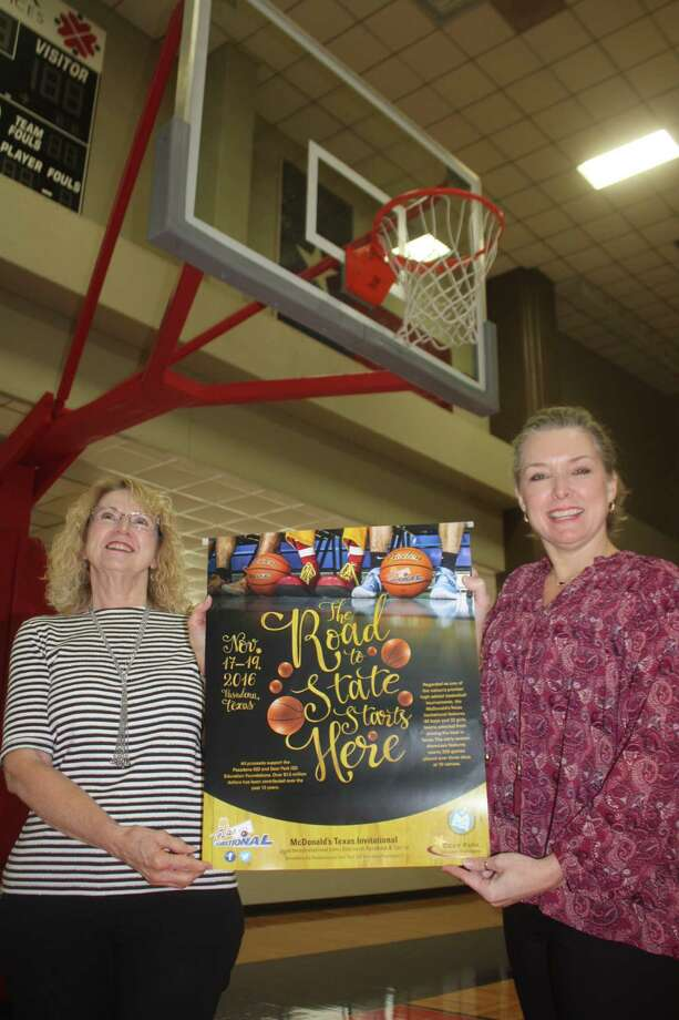 Ticket office employees Cathey Story (left) and Liz Tolleson display the McDonald's Texas Invitational  poster that's advertising this weekend's basketball extravaganza at 10 locations around town. Fans can see as many games as possible with a $20 weekend pass. They're on sale at the PISD administration building. Photo: Robert Avery