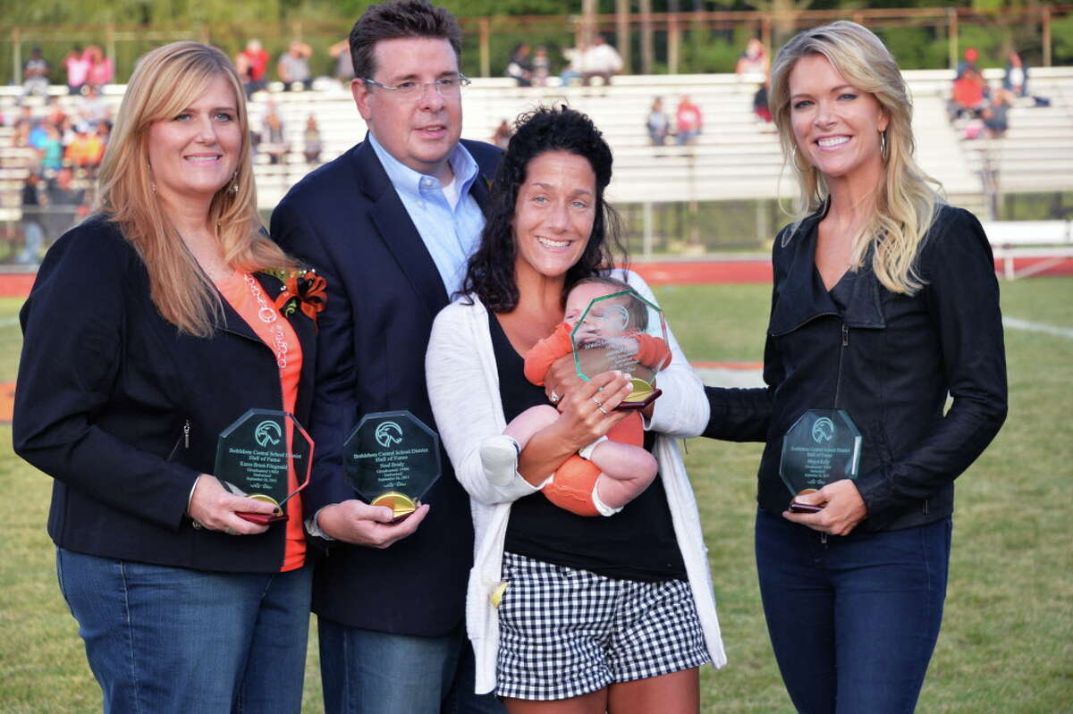 Four BCS alumni recognized for their contributions in sports, journalism, business and health care, from left, Karen Bruni-Fitzgerald, Neal Brady, Chris Quatraro and infant son George, accepting for her husband Matt Quatraro and Megyn Kelly during a Hall of Fame induction ceremony at Bethlehem Central High School Saturday Sept. 26, 2015 in Bethlehem, NY. (John Carl D'Annibale / Times Union)