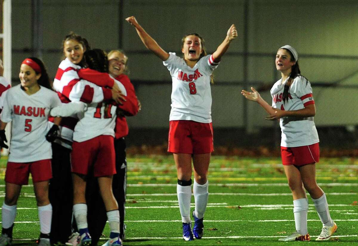 Masuk's Nikki Bisesi, center, cheers and celebrates with teammates after the Panthers beat Farmington in the Class L semifinals Wednesday in Meriden.