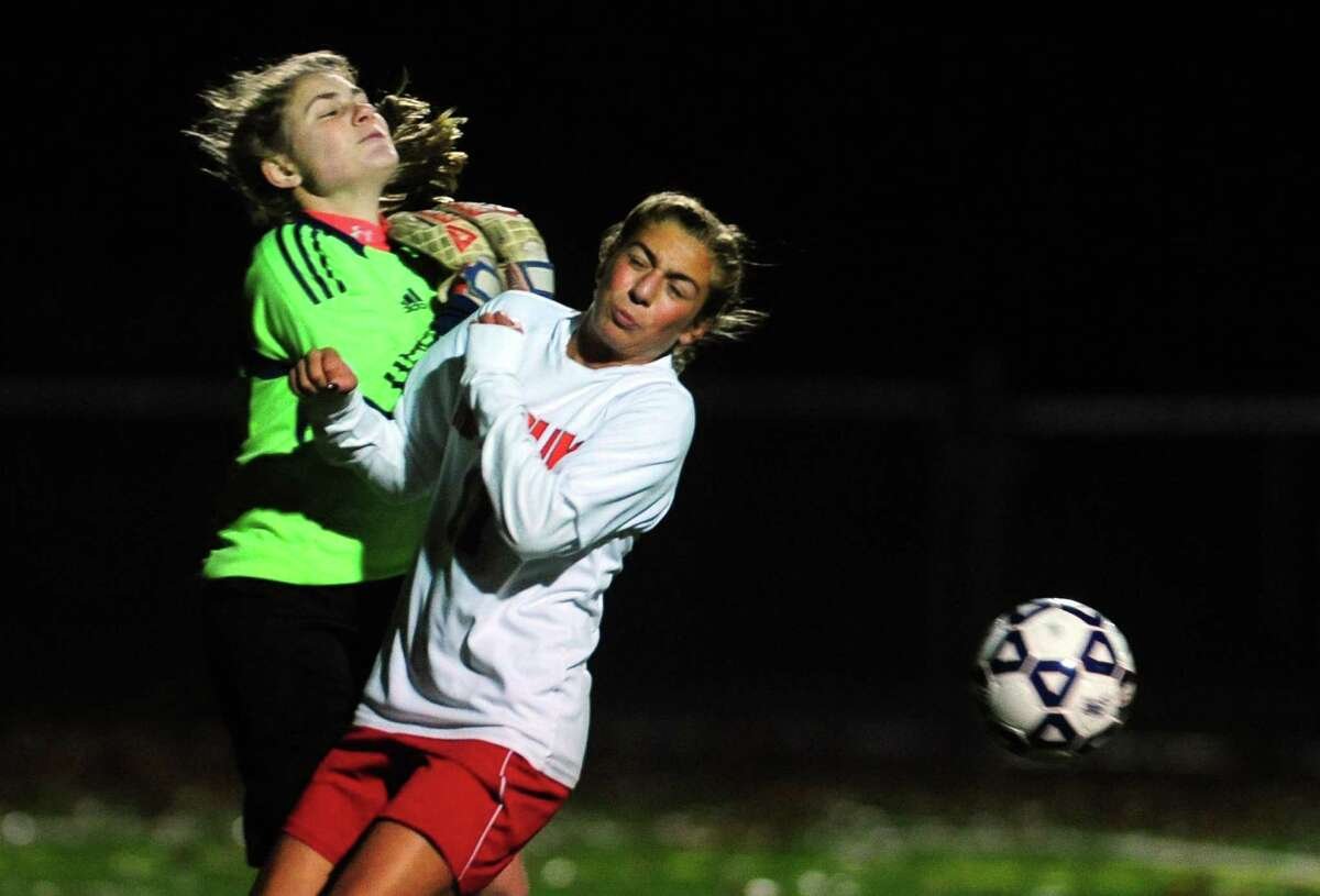 Masuk's Giavanna DeLorenzo collides with Farmington goalie Carolyn Ives during Class L soccer semifinal action Wednesday in Meriden.