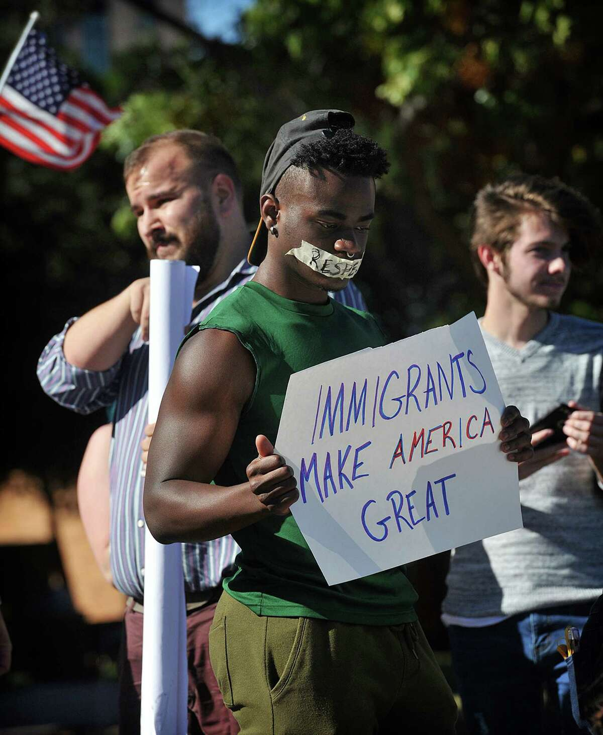 Midwestern State University nursing student Richard Brown was one of about 70 students who came out to stage a peaceful protest against hate, intolerance and president elect Donald Trump, on campus Wednesday afternoon in Wichita Falls, Texas. A smaller group held signs supporting Trump/Pence. (Torin Halsey/Wichita Falls Times Record News via AP)