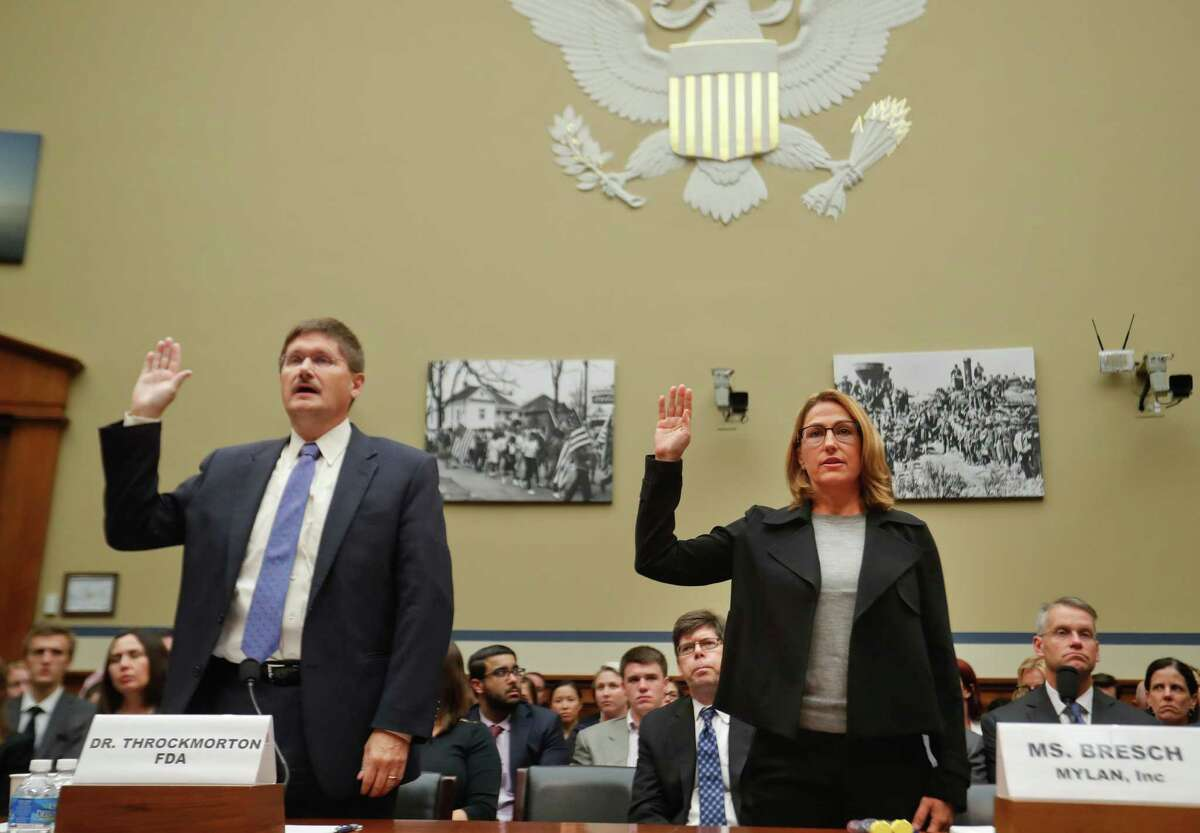 FILE - In this Wednesday, Sept. 21, 2016 file photo, Mylan CEO Heather Bresch, right, and Dr. Doug Throckmorton, deputy director, Center for Drug Evaluation and Research, Food and Drug Administration (FDA), are sworn in on Capitol Hill in Washington, prior to testifying before the House Oversight Committee hearing on EpiPen price increases. Bresch defended the cost for life-saving EpiPens, signaling the company has no plans to lower prices despite a public outcry and questions from skeptical lawmakers. (AP Photo/Pablo Martinez Monsivais)