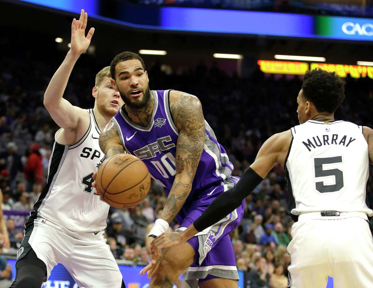 Sacramento Kings center Willie Cauley-Stein, center, passes between San Antonio Spurs' Davis Bertans, left, and Dejounte Murray, right, during the first quarter of an NBA basketball game Monday, Jan. 8, 2018, in Sacramento, Calif. (AP Photo/Rich Pedroncelli)