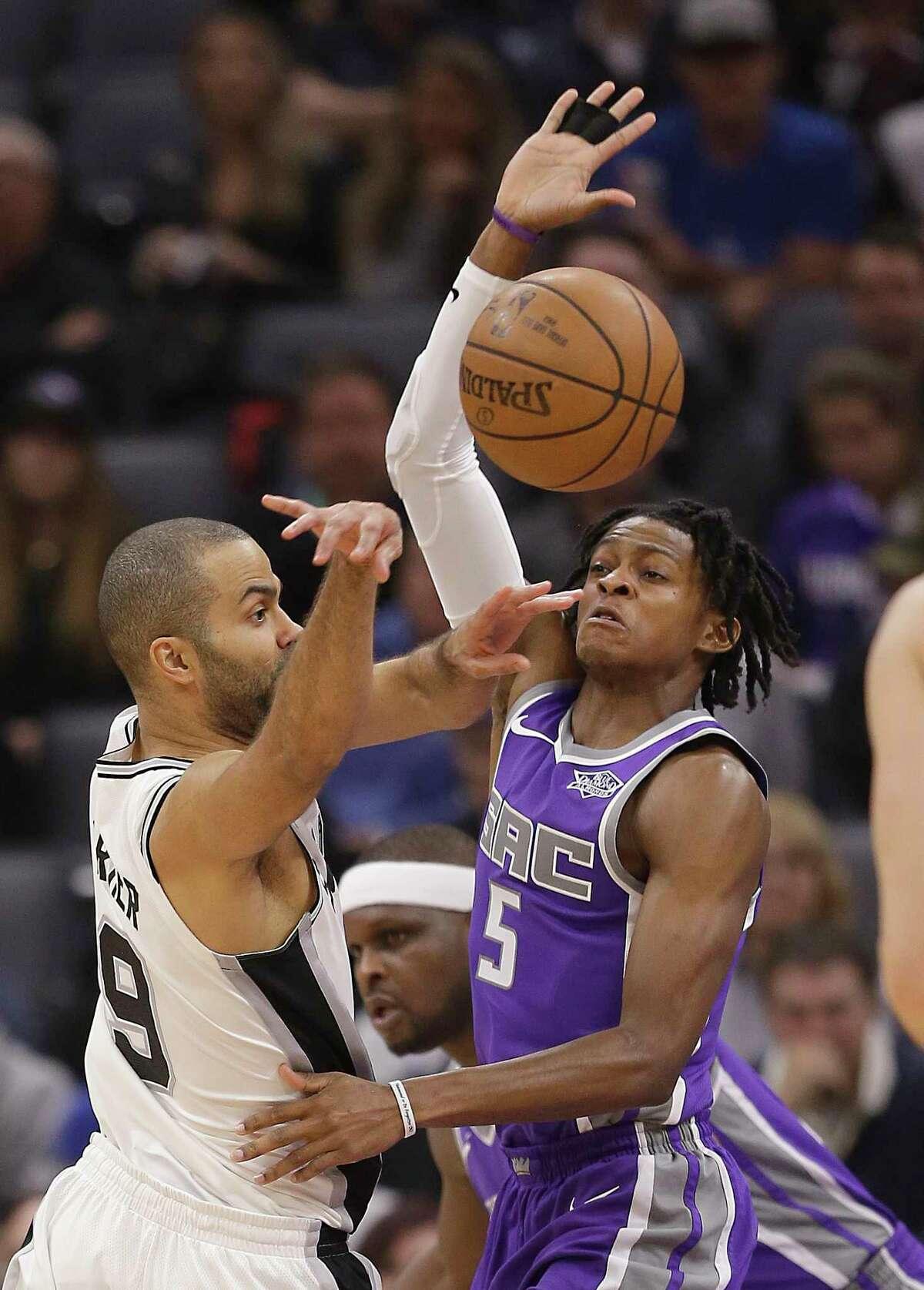 San Antonio Spurs guard Tony Parker, left, pass against Sacramento Kings guard De'Aaron Fox during the first quarter of an NBA basketball game Monday, Jan. 8, 2018, in Sacramento, Calif. (AP Photo/Rich Pedroncelli)
