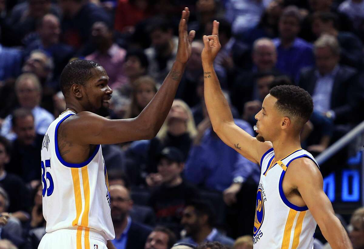 Kevin Durant #35 and Steph Curry #30 of the Golden State Warriors high five during the first half of an NBA game against the Toronto Raptors at Air Canada Centre on November 16, 2016 in Toronto, Canada.
