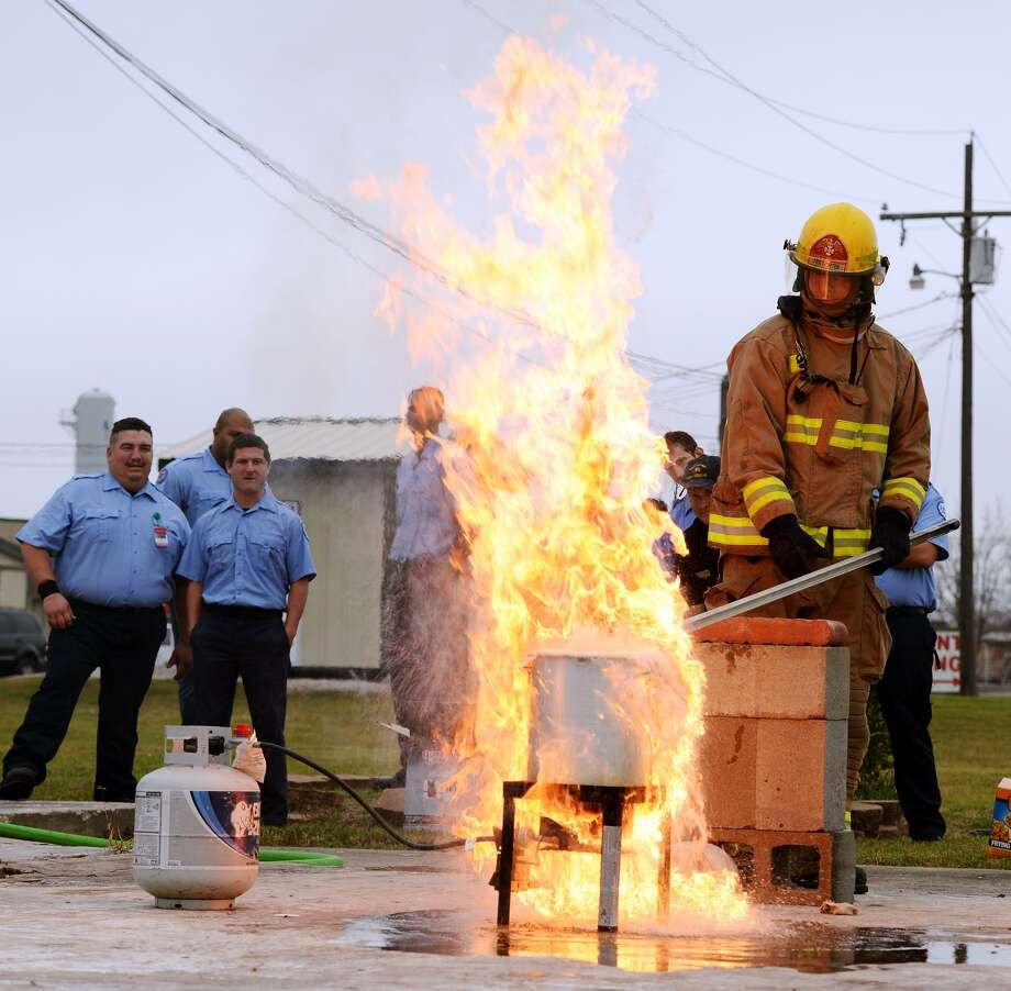 Fireman Andy Brown drops a frozen turkey into an overfilled pot of oil as it spills over and catches fire Friday morning. The Beaumont Fire Department demonstrated the dangers of improperly frying a turkey at their training facility Friday morning. Texas is ranked number one in the nation for turkey frying incidents. Photo taken Jake Daniels/@JakeD_in_SETX Photo: Jake Daniels / ©2013 The Beaumont Enterprise/Jake Daniels